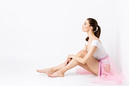 basque woman: Beautiful young woman in white bodysuit and pink basque sitting on floor over white backgound. Copy space.