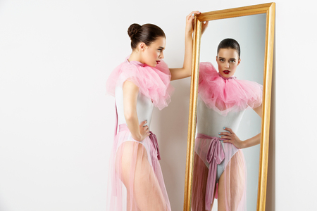 basque woman: Beautiful young woman in white bodysuit and pink basque standing near wall mirror