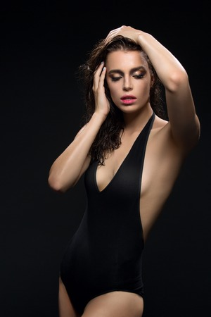 black woman lingerie: Beautiful wet young woman in black sexy swimwear. Over dark background. Copy space. Stock Photo