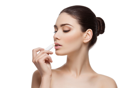 Beautiful young woman applying chapstick to lips. Isolated over white background. Copy space. Stock Photo