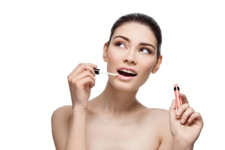 lipgloss: Beautiful young woman applying pink lipgloss to lips. Isolated over white background. Copy space.