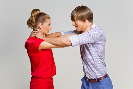 strangling: Young man and woman strangling each other. Over grey background.