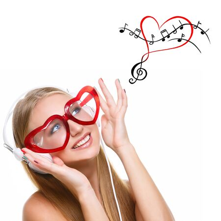 woman looking up: Beautiful young woman in big headphones and red heart shaped glasses looking up at musical notes drawing. Isolated over white background. Copy space. Square composition.