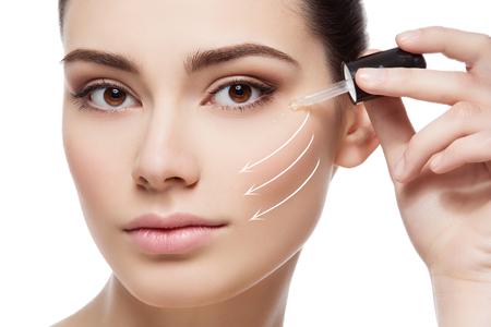 Bella giovane donna applicare idratante siero su zona degli occhi sotto. colpo di bellezza. Avvicinamento. Frecce di direzione. Isolato su sfondo bianco.