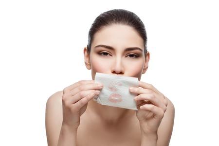 Mooie jonge vrouw afvegen lippen met weefsel voor langdurige lippenstift. Geïsoleerde over witte kronkelen. Kopieer ruimte. Stockfoto