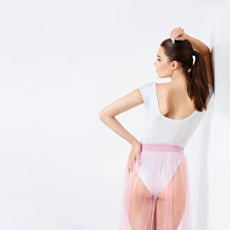 bodysuit: Beautiful young woman in white bodysuit and pink basque standing near wall. Copy space. Square composition.