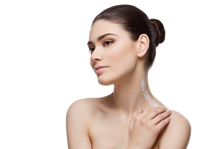 Beautiful young woman applying moisturizing cream to neck and shoulder. Isolated over white background. Copy space. Stock Photo