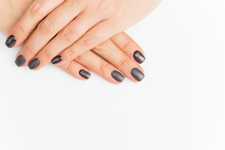 grey nails: Woman hands with grey nails manicure. Over white background. Copy space.