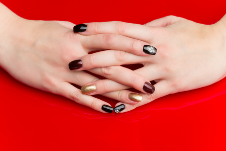 red nail colour: Woman hands with manicure. Multicolored nails. Copy space. Over red background.
