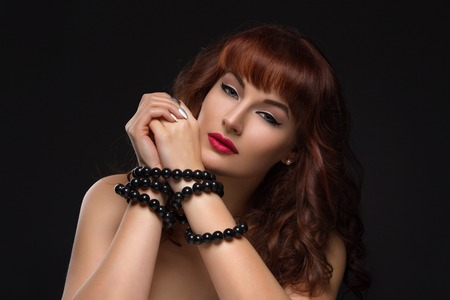 tied up: Closeup of beautiful young woman with bright red lips and hands tied up. Over black background. Stock Photo