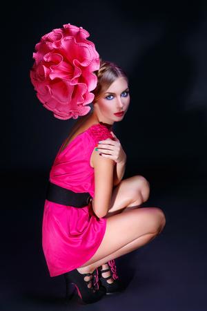 labios sensuales: Hermosa mujer joven con gran flor rosa en la cabeza. Sobre fondo oscuro. maquillaje brillante. Espacio de la copia.