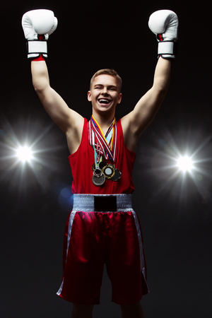 boxing glove: Teen boxer in red top and boxers with many medals lifting up hands in box gloves. Over dark background with lights.