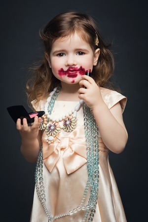 putting lipstick: Beautifil little girl in dress and accessories putting lipstick all over her face. Over dark background. Stock Photo