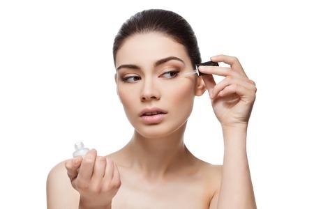 Belle jeune femme appliquant sérum hydratant anti-vieillissement de la sous région des yeux. Isolé sur fond blanc. Copiez espace.