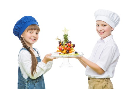 selfmade: Little boy and girl holding tree shape fruit snack selfmade. Isolated over white background. Copy space.