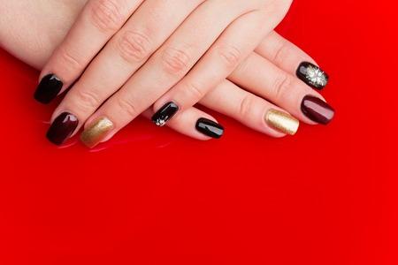 background elegant: Manos de mujer con manicura. u�as multicolores. Espacio de la copia. Sobre fondo rojo.