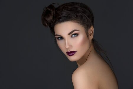 beauty shot: Beautiful young woman with dark red lips and hairdo. Beauty shot. Over grey background.