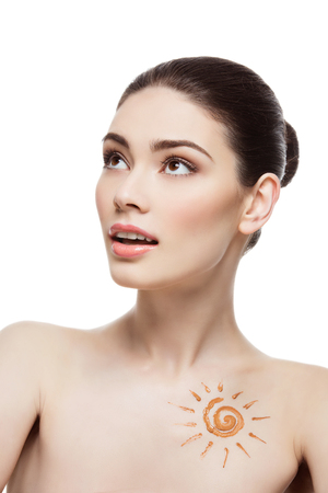 face to face: Beautiful young woman with tan bronze cream sun shape drawing on chest. Isolated over white background.
