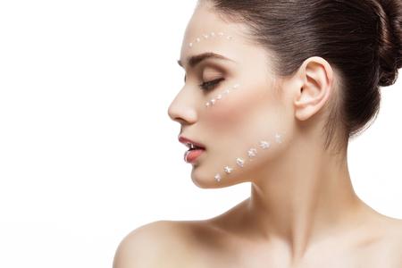 Mooie jonge vrouw met vochtinbrengende crème stippen op het gezicht. Geïsoleerde over witte achtergrond.