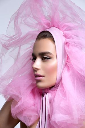 head wear: Beautiful young woman in fluffy pink head wear. Stock Photo
