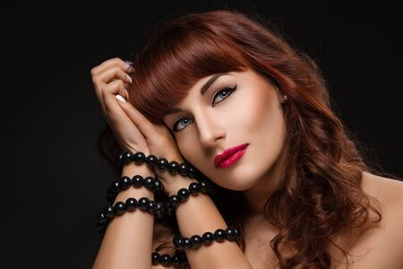 tied woman: Closeup of beautiful young woman with bright red lips and hands tied up. Over black background. Stock Photo