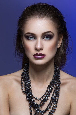 beauty shot: Beautiful young woman with bright makeup and beads. Beauty shot. Copy space.
