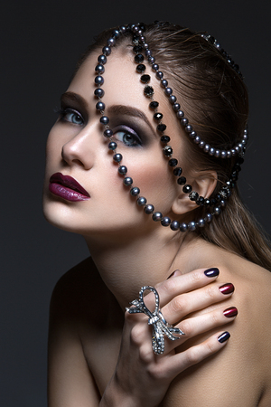 vogue style: Beautiful young woman with bright makeup and beads on head. Beauty shot. Copy space. Stock Photo
