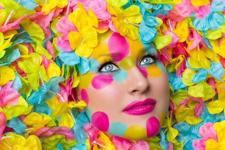 face paint: Closeup of young woman face in colorful flower petals. Beauty shot. Face paint.