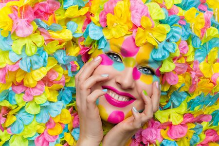 beauty shot: Closeup of young woman face in colorful flower petals. Beauty shot. Face paint.