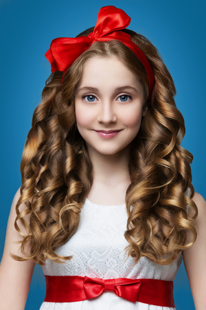 Beautiful teenage girl with curly hair and red rebbon looking like doll. Over blue backgroound. Standard-Bild