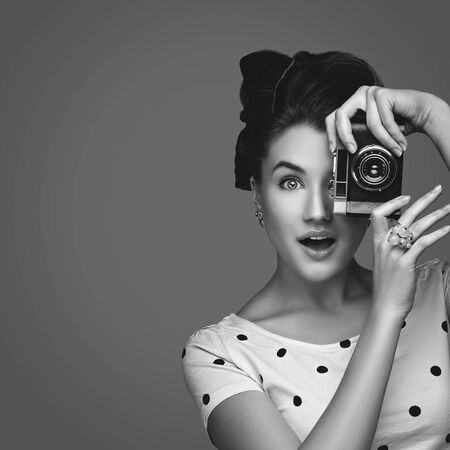 monocrome: Beautiful young woman with retro photo camera. Surprised expression. Closeup portrait. Monocrome. Copy space. Square composition. Stock Photo