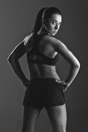 black backgound: Sporty fit beautiful woman with muscle relief. Over black backgound. Copy space.