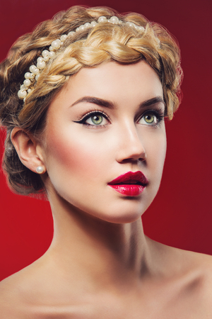 beauty shot: Beautiful young woman with full red lips and braid hairstyle. Beauty shot over red background.
