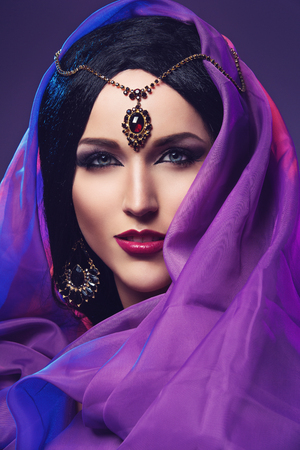 Beautiful young woman with eastern style bright makeup. Beauty shot. Copy space.