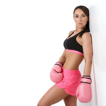 sportwear: Beautiful sporty fit young woman in sportwear and pink boxing gloves. Square composition. Copy space. Stock Photo