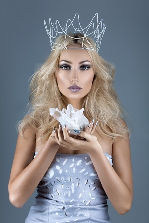 Beautiful young woman in crown holding crystal stone. Copy space. Stock Photo - 56088447