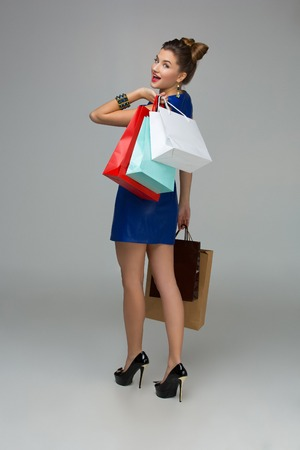 Smiling young woman in blue dress with multiple shopping bags. Happy expression. Over grey background. Copy space.