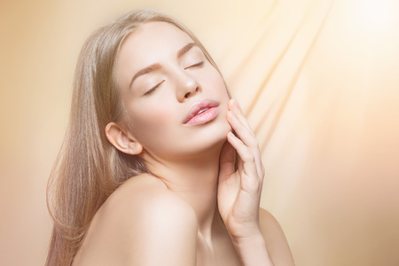 touching face: Beautiful young woman with perfect skin and shiny hair touching face over beige background. Beauty shot. Copy space.