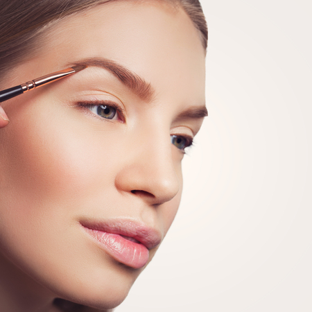 Beautician correcting eyebrows form on beautiful woman face. Beauty shot. Close-up. Isolated. Copy space. Square composition. Standard-Bild