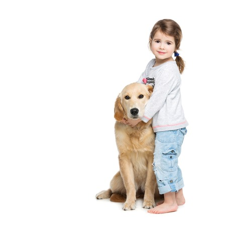 amigos abrazandose: Beautiful little girl hugging golden retriever puppy. Child and dog. Isolated over white background. Copy space. Foto de archivo