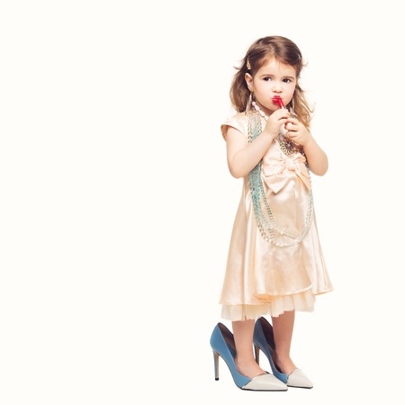 Beautiful small girl in dress and mother's high heels applying red lipstick. Isolated over white background. Copy space. Standard-Bild