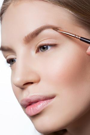 correcting: Beautician correcting eyebrows form on beautiful woman face. Beauty shot. Close-up.