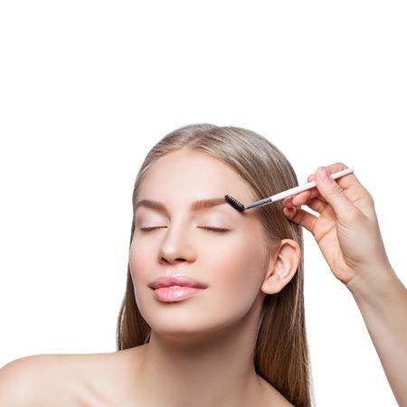 correcting: Beautician correcting eyebrows form on beautiful woman face. Beauty shot. Close-up. I