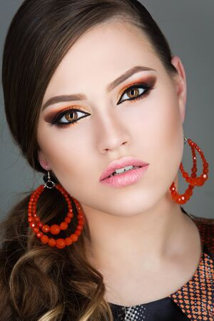 beauty shot: Beautiful young woman with bright orange makeup. Beauty shot. Closeup.