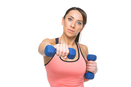 sportwear: Beautiful sporty woman in sportwear making exercise with blue dumbbells. Isolated over white background. C