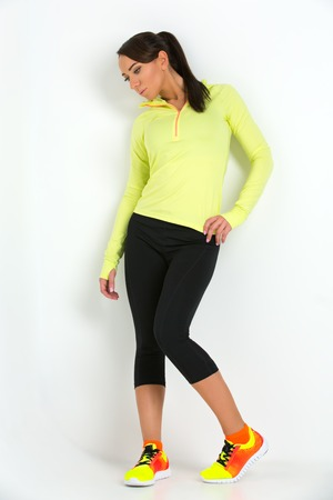 sportwear: Beautiful sporty fit young woman in green and black sportwear over white background.