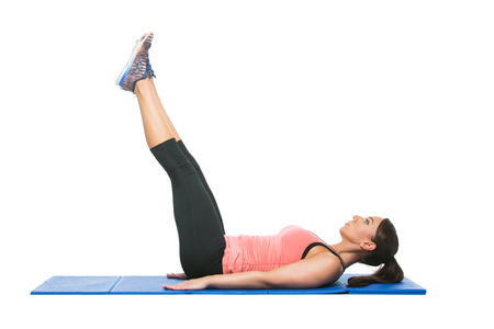 Beautiful young fit sporty woman making sport exercise on blue mat. Isolated over white background. Copy space.