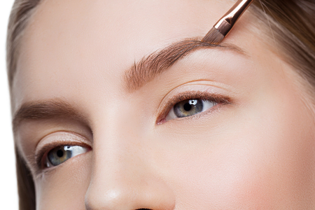 Schoonheidsspecialiste corrigeren wenkbrauwen vormen op mooie vrouw gezicht. Schot van de schoonheid. Detailopname.