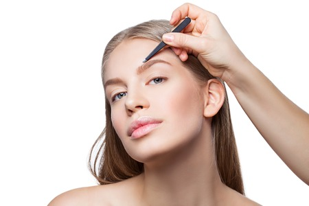 Beautician correcting eyebrows form on beautiful woman face. Beauty shot. Close-up. Isolated. Copy space. Standard-Bild
