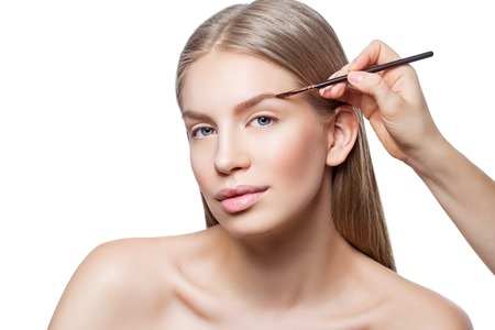 Beautician correcting eyebrows form on beautiful woman face. Beauty shot. Close-up. Isolated. Copy space. Stock Photo